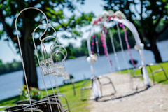 Lakeside wedding ceremony. Wedding arch and decorations, selecti Royalty Free Stock Image