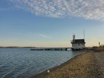 Lakesidesikt med ett livräddarehus på den tomma stranden Arkivfoto