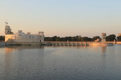Lakhota Fort and causeway at Sunset. This small palace, on an island in the middle of Lakhota Lake, once belonged to the Maharaja of Nawanagar. This fort-like Stock Images