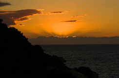Lakka sunset. The end of a sunset in Lakka Paxos, with the rays of the sun popping out over the clouds Stock Photo