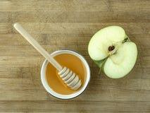 Lakonisk stilleben för det judiska nya tefatet för år-en med honung och halva ett äpple på en grov träyttersida Arkivbild