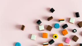 LakritsrotAllsorts sötsaker på rosa bakgrund kopiera avstånd royaltyfria foton