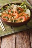 Laksasoep met garnalen, noedels, spruiten en koriander in een boog stock afbeelding