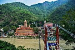 Lakshman jhula suspension bridge in Rishikesh with boats in ganga river haridwar and rafting stock images