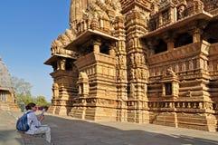 Lakshmana Temple, Khajuraho, India. Khajuraho, Madhya Pradesh , India - March 2011 :  Foreign visitor studying at Lakshmana Temple, dedicated to Lord Vishnu Stock Photography