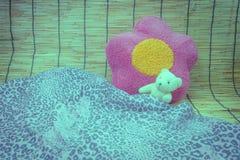 Lali niedźwiadkowy biały dosypianie na kwiecistych poduszkach na tło bambusie Obrazy Stock