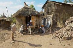 People paint and read at the house entrance in Lalibela, Ethiopia. LALIBELA, ETHIOPIA - JANUARY 27, 2010: Unidentified people paint and read at the house Stock Photo