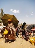 Lalibela Etiopien, 13th Juni 2009: Kvinna som går tillbaka från mars royaltyfri foto
