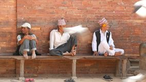 LALITPUR, NEPAL - 7 de Bejaarde mensen van OKTOBER 2018 op bank dichtbij steenbeeldhouwwerk Etnische rijpe mensen op bank op stra stock videobeelden
