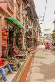 Lalitpur, Nepal - 3 de novembro de 2016: Opinião da rua com lojas de lembrança e os povos nepaleses de passeio na cidade do metro foto de stock