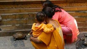 LALITPUR, NEPAL - 7 DE OCTUBRE DE 2018 mujeres que alimentan la tortuga en la calle Mujeres en ropa nacional colorida con el bebé metrajes