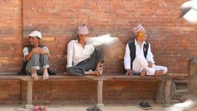 LALITPUR, NEPAL - 7 DE OCTUBRE DE 2018 personas mayores en banco cerca de la escultura de piedra Gente madura étnica en banco en  almacen de metraje de vídeo