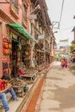 Lalitpur, Nepal - 3 novembre 2016: Vista della via con i negozi di ricordo e la gente nepalese di camminata nella città del metro fotografia stock