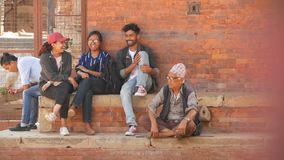 LALITPUR, NEPAL - 7 OCTOBER 2018 Ethnic people on street of ancient city, Group of young people and senior man on brick. Steps on street of Patan city stock footage