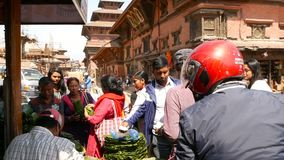Lalitpur, Nepal - 7 October 2018 People surrounding stall and buying small ritual plates for rituals on royal Durbar. Square, Kathmandu. Daily life, oriental stock footage
