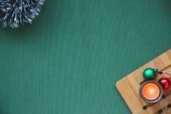 Lamé del ` s del nuovo anno, palle, una candela bruciante su un supporto di legno su un fondo verde Posto per l'iscrizione Fotografie Stock