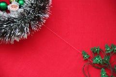 Lamé, ghirlanda, palle e Santa Claus del ` s del nuovo anno su un fondo rosso Posto per l'iscrizione Immagini Stock