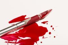 Lama del bisturi con sangue Fotografie Stock