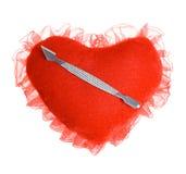 Lama per il manicure su un cuore della peluche Fotografia Stock