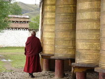 A Lama rolling Tibet barrel. In a temple at west of China,an old man was rotating the golden barrel for praying Stock Image