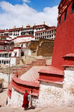 Lama walking at colorful Ganden Monastery Stock Photos