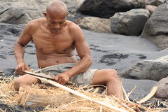Lamalera whaler working on a beach. A whaler from Lamalera village prepares wood on a beach. Villagers of Lamalera on Lembata island, East Indonesia, are the Royalty Free Stock Photo