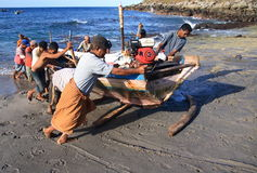 Lamalera Whalers, die ein Boot drücken Lizenzfreie Stockbilder