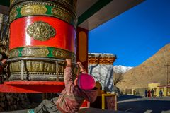 A LITTLE BOY PLAYS WITH PRAYER WHEEL IN LAMAYURU MONASTERY royalty free stock photography