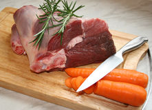 Lamb. A joint of lamb ready for cooking,with carrots and rosemary Stock Image