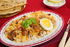 Lamb Biryani. A festive Indian curry, lamb biryani with crisp onion rings, coriander and egg, with chapatis and chutney royalty free stock image