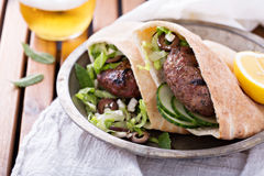 Lamb burgers in a pita. Grilled, lamb burgers in a pita with cucumbers, olives and salad stock photo