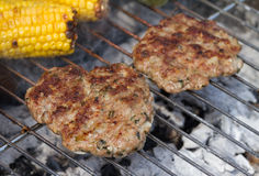 Lamb Burgers. Sizzling Minted Lamb Burgers on Grill with Corn Cobs Stock Photography