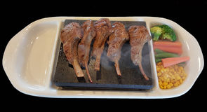 Lamb chop Steak on extremely hot volcano rock plate Royalty Free Stock Photography