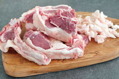 Lamb chopRaw lamb chops and fat on a olive wood cutting board on a grey abstract background. Healthy cooking concept. stock image