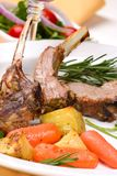 Lamb chops. (ribs) with Rosemary garlic dressing, garnished with baby carrots, potatoes and rosemary sprigs. Dinner settings Stock Photo