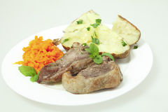 Lamb chops carrots and baked potato plate Royalty Free Stock Photos
