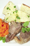 Lamb chops carrots and baked potato vertical Royalty Free Stock Images