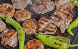 Lamb chops with garnish on grill. Close-up photograph of grilled meat with greenpepper and mushroom Royalty Free Stock Photos
