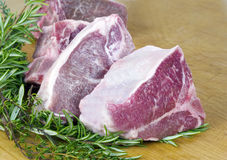 Lamb Chops - horizontal. Thick sliced loin lamb chops on wood chopping block with fresh rosemary and thyme sprigs royalty free stock image