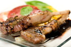 Lamb Chops on plate. Lamb chops with balsamic vinegar reduction served with a heirloom tomato salad stock photos