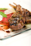 Lamb Chops on plate. Lamb chops with balsamic vinegar reduction served with a heirloom tomato salad royalty free stock photos