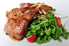 Lamb Chops with Salad. Lamb chops and green salad with baby tomatoes on a plate in a restaurant Royalty Free Stock Images