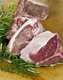 Lamb Chops - vertical. Thick sliced loin lamb chops on wood chopping block with fresh rosemary and thyme sprigs stock images