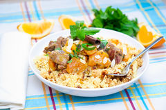 Lamb Cous Cous. A plate with delicious looking cous cous with lamb meat, apricots, almonds, raisins, dates, cinnamon and mint. I used some mint leaves and orange Royalty Free Stock Photography