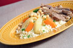 Lamb with couscous. Sticky lamb with couscous, garnished with spring potatoes carrots and chickpeas Royalty Free Stock Photos