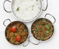 Lamb curries and rice from above. A bowl of spiced lamb curry with coriander leaves and slivers of red and green chillies, next to a bowl of Lahore-style lamb stock photos