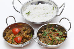 Lamb curries and rice s3erving bowls. A bowl of spiced lamb curry with coriander leaves and slivers of red and green chillies, next to a bowl of Lahore-style royalty free stock photo
