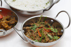 Lamb curry night. A bowl of spiced lamb curry with coriander leaves and slivers of red and green chillies, next to a bowl of Lahore-style lamb curry with split royalty free stock photo