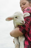 Lamb and farm girl. Pet lamb being held by farm girl Royalty Free Stock Photography