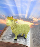 Lamb of god on bible. Photo of a lamb wearing a crown standing on bible...depicting jesus who takes sin away from world.sky area ideal for text etc Stock Photo